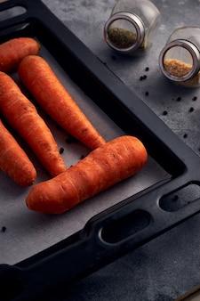 Gros plan de quelques carottes dans une plaque de cuisson