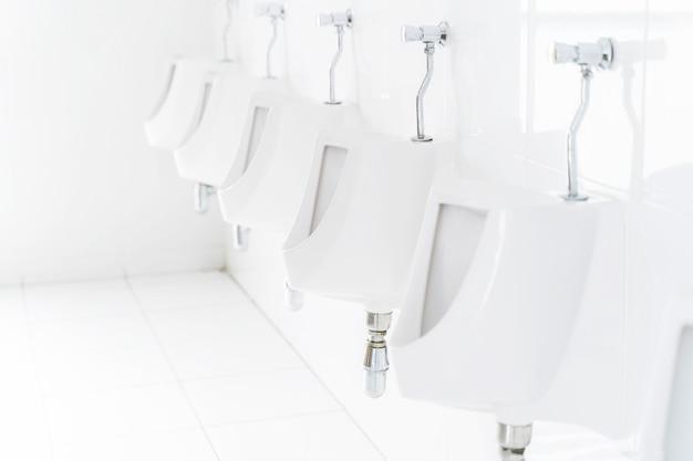Gros plan de la rangée d'urinoirs dans les toilettes publiques.