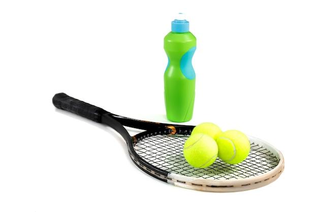 Gros plan sur une raquette de tennis, des balles et une bouteille d'eau sur blanc