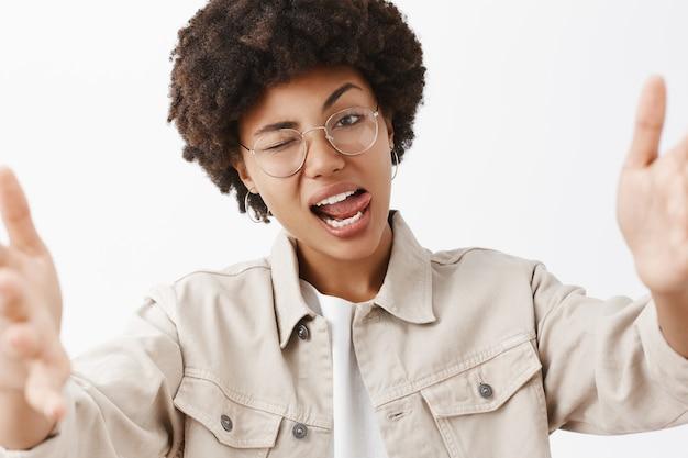 Gros plan de rebelle confiant et lesbienne afro-américaine cool à lunettes et chemise beige, montrant la langue flirty et clignant de l'œil, tirant les mains vers, séduisant quelqu'un