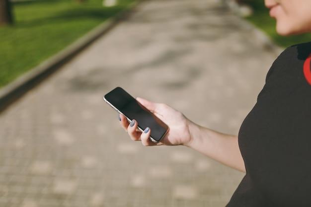 Gros plan recadré de mains de femme tenant et utilisant un téléphone portable, smartphone avec écran vide vide dans le parc de la ville à l'extérieur