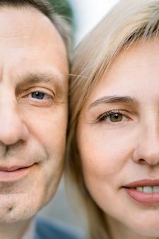 Gros plan recadré de la moitié des visages d'un bel homme d'âge moyen et d'une superbe femme blonde séduisante, regardant la caméra avec de jolis sourires