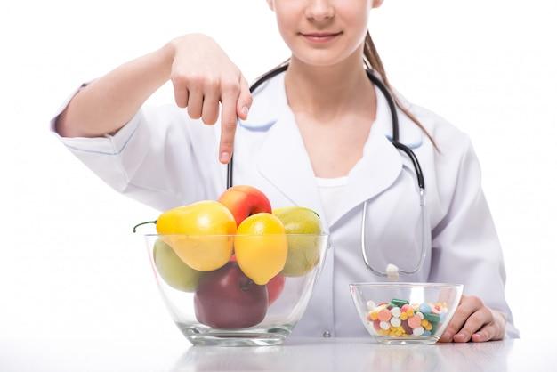 Gros plan d'un récipient en verre avec des fruits et un autre avec des pilules.