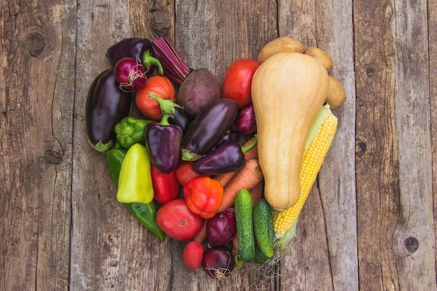 Gros plan sur une récolte de légumes frais en forme de cœur, une récolte de fermier, un potager. eco-produits, végétarisme, protéines alternatives, nutrition végétale
