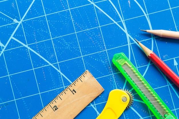 Gros plan de règle, ciseaux, cutter, crayon sur tapis de découpe bleu.