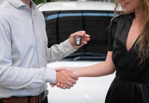 Gros plan de remettre les clés d'une voiture à un jeune homme d'affaires.