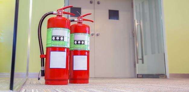 Gros plan sur le réservoir des extincteurs rouges à la porte de sortie du bâtiment.