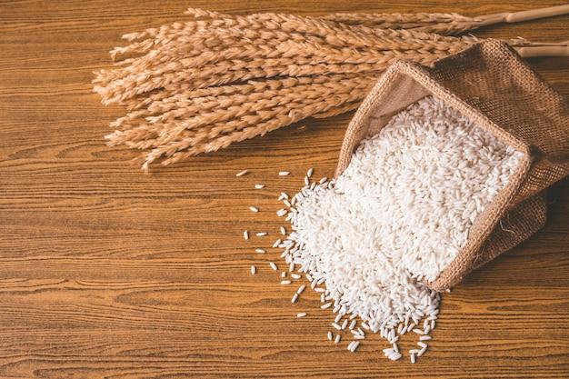 Gros plan de riz cru dans le sac de jute sur la table en bois.