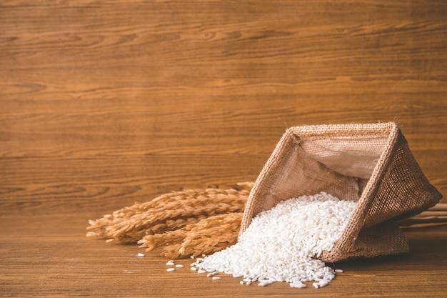 Gros plan de riz cru dans un sac de toile de jute sur une table en bois.