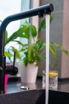 Gros plan sur un robinet de cuisine avec de l'eau courante sur fond de plantes vertes en pot sur un rebord de fenêtre