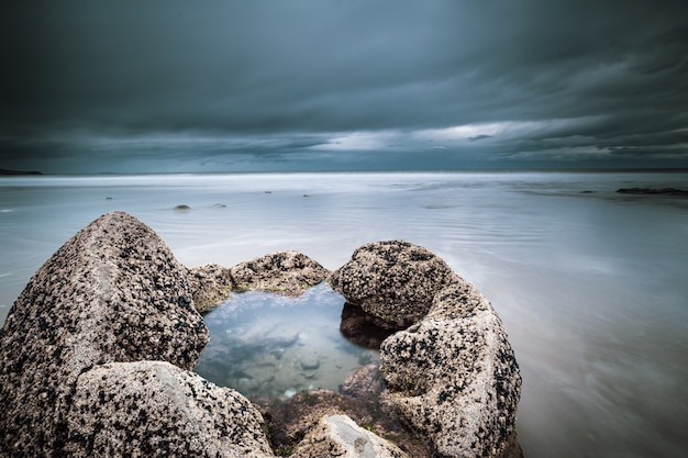 Gros plan d'un rocher rempli au milieu de la mer sous un ciel bleu nuageux