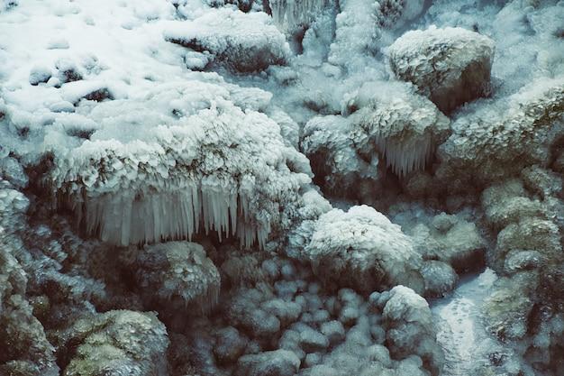 Gros plan de roches couvertes de neige et de glace sous la lumière du soleil en hiver