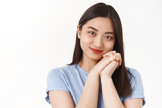 Gros plan romantique tendre touché jeune fille brune asiatique serrer les mains ensemble étonné merveilleuse belle scène soupir heureux souriant ravi réconfortant sentiment debout beau mur blanc