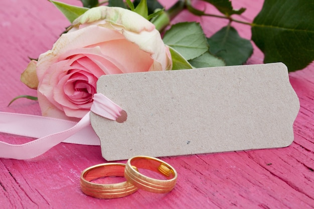 Gros plan d'une rose rose, une balise avec un espace pour le texte et deux anneaux de mariage en or sur une table rose