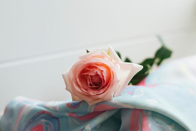 Gros plan d'une rose rose sur une couverture