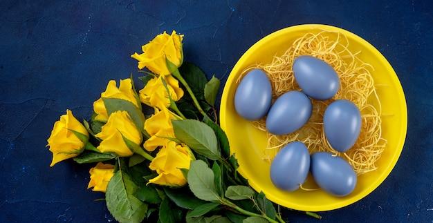 Gros plan des roses jaunes et des oeufs de pâques dans une assiette sur fond bleu foncé branché