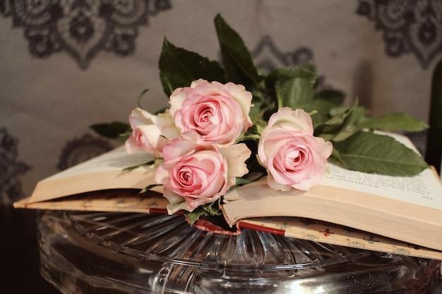 Gros plan de roses roses sur un livre ouvert
