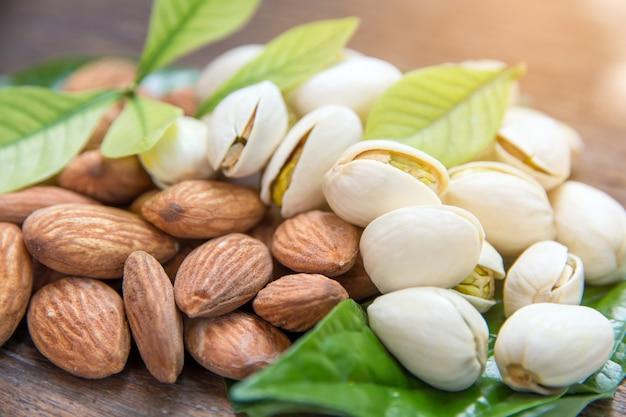 Gros plan de rôti de grain d'amandes et noix de pistaches sur fond de bois avec des feuilles vertes