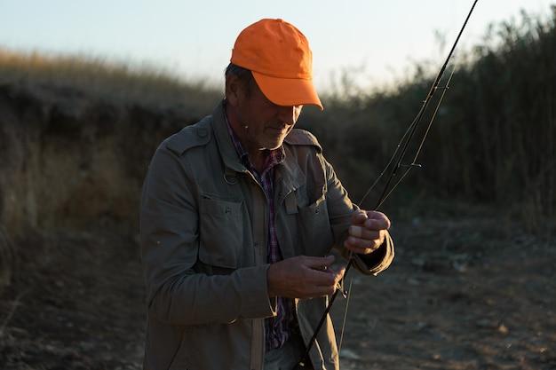 Gros plan de roue de canne à pêche, homme pêchant avec un beau coucher de soleil.