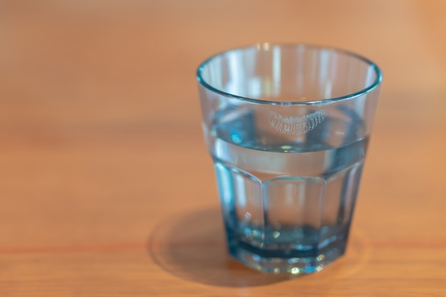 Gros plan, rouge à lèvres, sur, verre eau, de, femme, boisson, sur, table bois