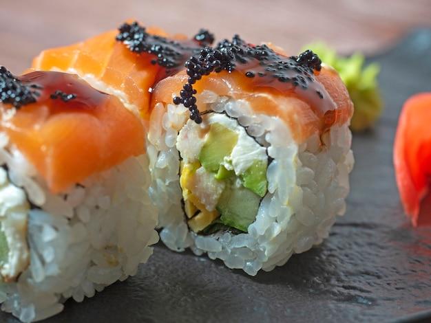 Gros plan d'un rouleau de sushi sur une plaque noire. cuisine japonaise traditionnelle