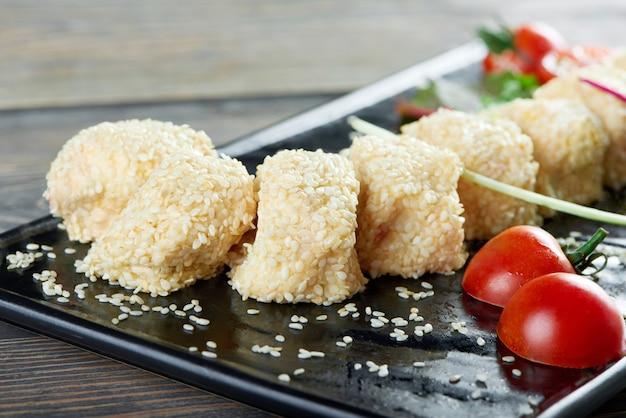 Gros plan de rouleaux de fromage avec du sezam sur une plaque noire servie avec des tomates cerises menu du restaurant copyspace nourriture délicieuse manger apéritif faim appétit café concept.