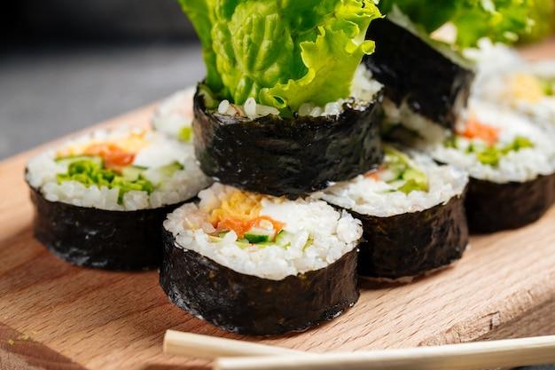 Gros plan sur les rouleaux de riz aux algues coréen gimbap sur la planche de bois avec de la sauce soja
