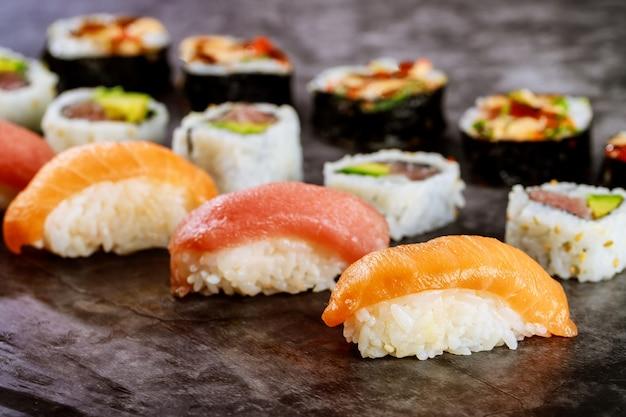 Gros plan de rouleaux de sushi au saumon rouge sur une surface noire. cuisine japonaise traditionnelle.