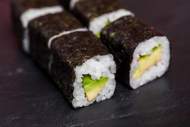 Gros plan de rouleaux de sushi à l'avocat sur fond d'ardoise noire