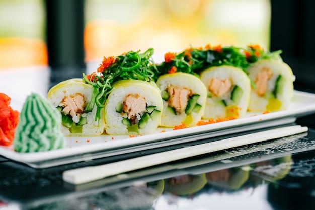 Gros plan de rouleaux de sushi avec du saumon frit et du concombre garni d'algues et de tobiko rouge
