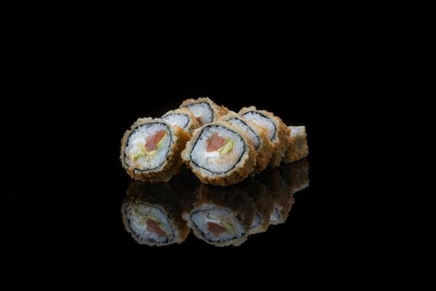 Un gros plan de rouleaux de sushi frits alimentaires isolés sur la réflexion noire
