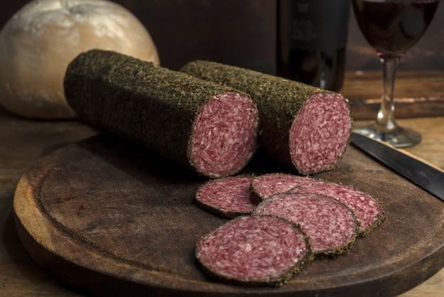 Gros plan sur des rouleaux de viande de salami fumé sur une planche de bois