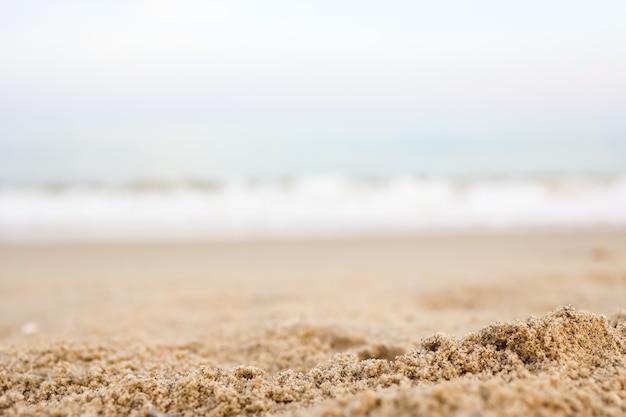 Gros plan sur le sable avec un fond de ciel de mer flou, une journée d'été, un espace de copie ou pour le produit.