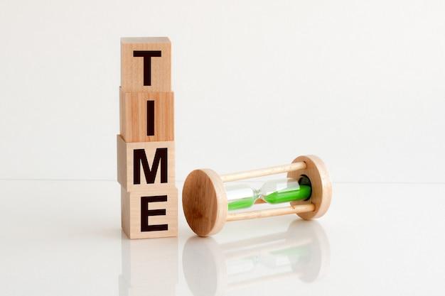 Gros plan d'un sablier à côté de blocs de bois avec l'heure du texte