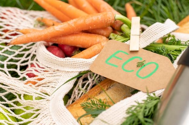Gros plan sac réutilisable avec épicerie sur l'herbe