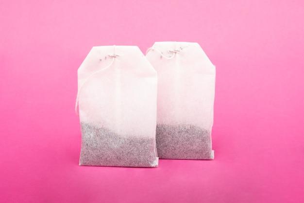 Gros plan des sachets de thé en tissu sur fond rose