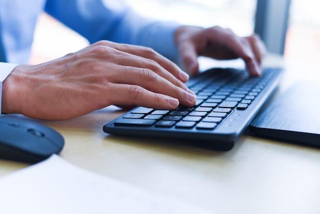 Gros plan de la saisie de la main masculine sur le concept de clavier - homme d'affaires travaillant sur le clavier et la souris ordinateur homme assis sur la table et en utilisant la technologie internet au lieu de travail au bureau