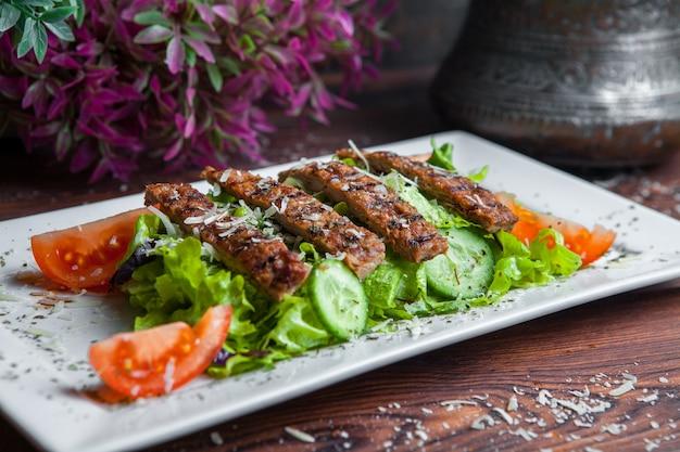 Gros plan d'une salade césar avec de la laitue fraîche, du parmesan, des croûtons frits et du rôti de bœuf