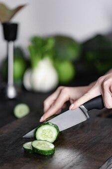 Gros plan d'une salade de coupe de main de femme sur une planche de bois à découper avec un couteau tranchant