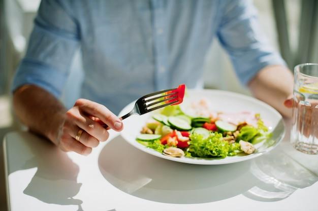 Gros plan d'une salade fraîche de laitue, concombre et tomate sur assiette pour une alimentation saine.