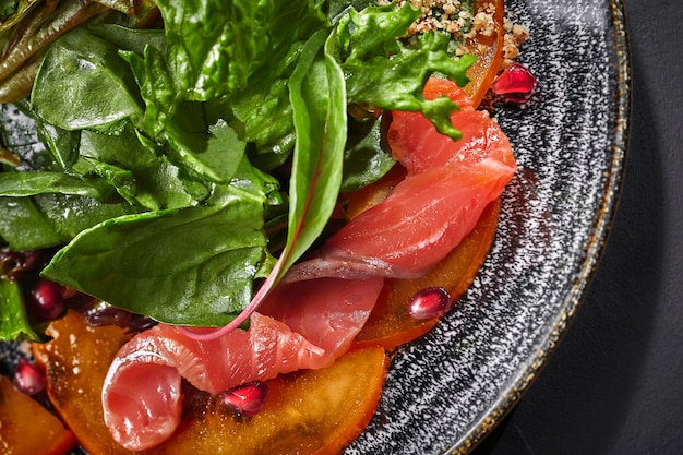 Gros plan de salade de kaki saumon verts noix de grenade