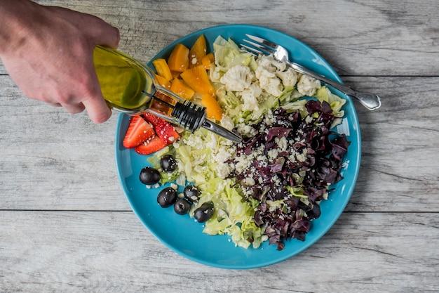 Gros plan d'une salade de légumes et de fruits avec une personne versant de l'huile végétale dessus