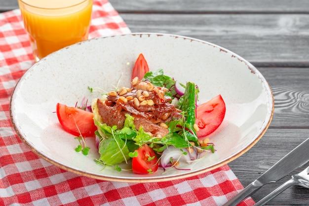 Gros plan d'une salade verte avec un steak de filet mignon tranché