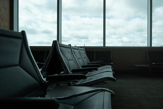 Gros plan sur la salle d'embarquement de l'aéroport vide, fenêtres avec nuages, espace de copie.