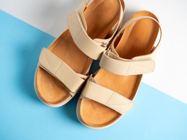 Gros plan de sandales en cuir beige sur fond blanc et bleu. une paire de chaussures, chaussures d'été pour femmes, vue de dessus, mise à plat.