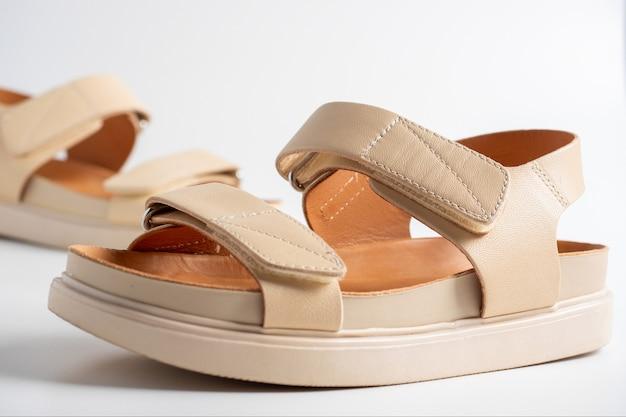 Gros plan de sandales en cuir beige sur fond blanc. paire de chaussures, chaussures de vol pour femmes