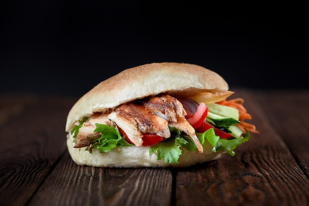 Gros plan d'un sandwich au kebab sur fond en bois