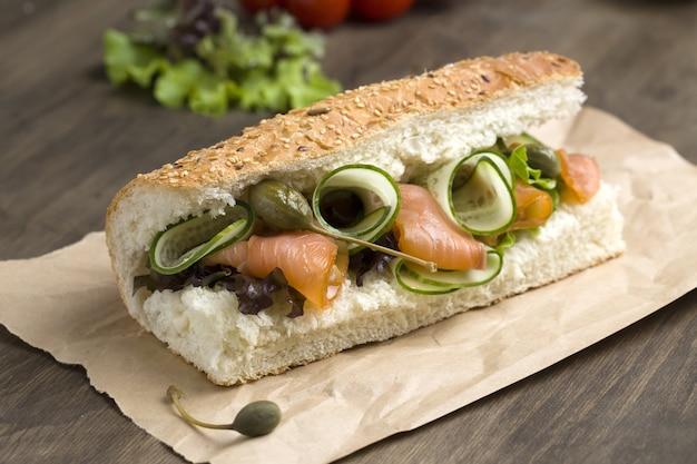 Gros plan d'un sandwich au saumon avec des légumes frais dans un pain baguette