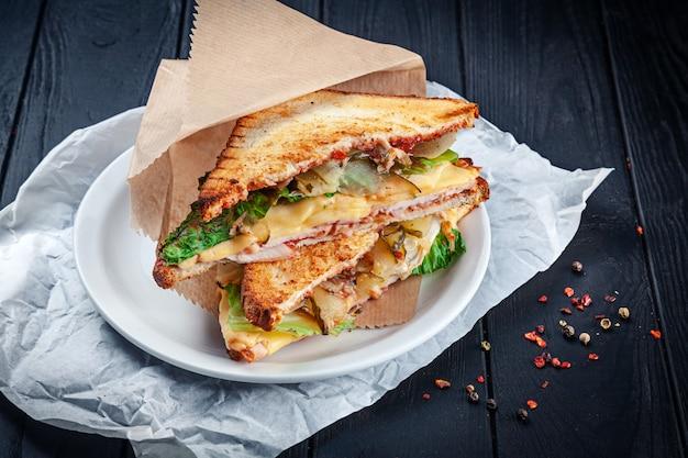 Gros plan sur un sandwich grillé avec du poulet et du fromage fondu et de la laitue