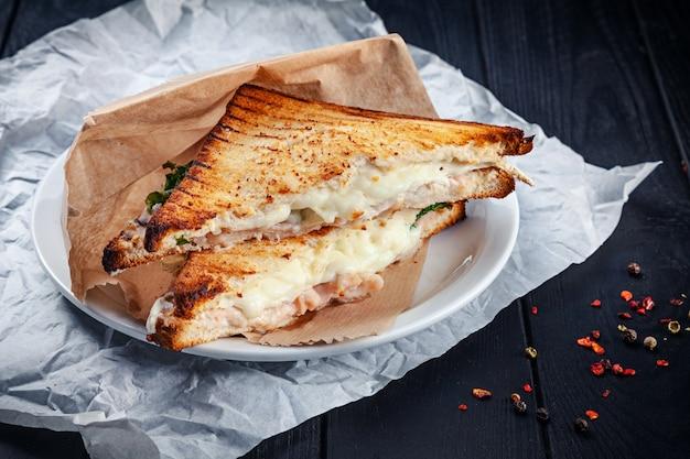 Gros plan sur un sandwich grillé avec du saumon et du fromage fondu et de la laitue